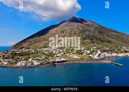 Italy, Sicily, Aeolian Islands, listed as World Heritage by UNESCO, Stromboli island, the active volcano Stromboli overlooking the village (aerial view) - Stock Photo