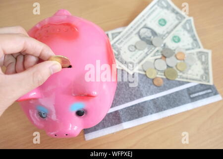 Close-up Of Hand Putting Coin In Piggy Bank On Table - Stock Photo