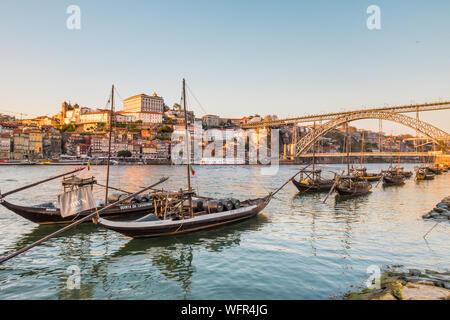 Sunset over the Duoro River in Vila Nova de Gaia Portugal with Dom Luis Bridge in the background - Stock Photo