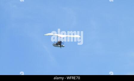 Low Angle View Of People Sitting In Hand Gliding Boat Against Sky - Stock Photo