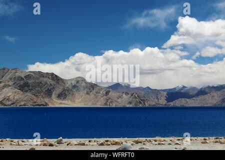 Scenic View Of Lake Against Mountains And Blue Sky - Stock Photo