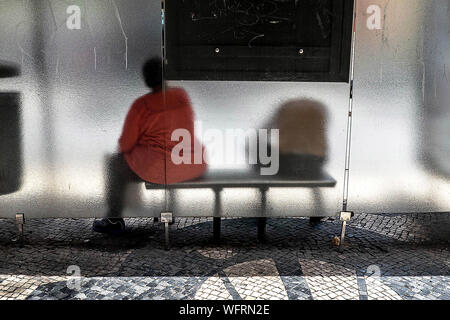 Rear View Of Man And Woman At Bus Stop Seen Through Glass - Stock Photo