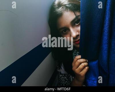Portrait Of Teenage Girl Sitting Behind Curtain - Stock Photo