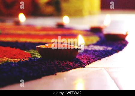Close-up Of Lit Diyas On Rangoli At Home - Stock Photo