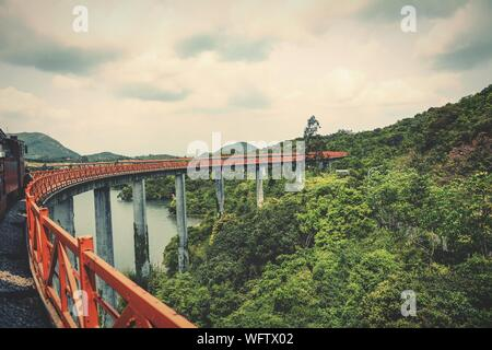 Train On Bridge Over Lake By Trees Against Cloudy Sky - Stock Photo