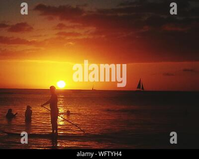 Silhouette People Standing In Sea Against Sky During Sunset - Stock Photo