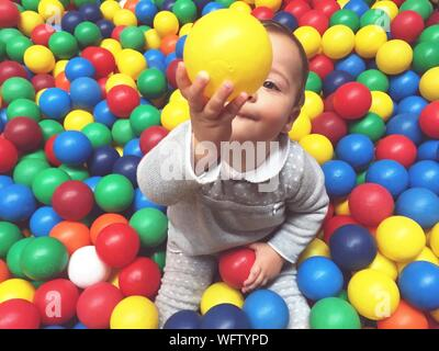 High Angle View Of Baby Boy Playing With Colorful Balls - Stock Photo