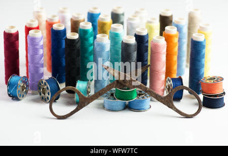 Close-up Of Rusty Scissor With Multi Colored Thread Spools Over White Background - Stock Photo