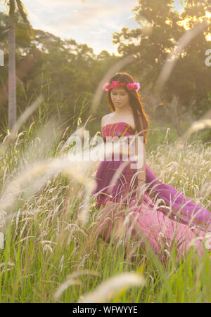 Young Woman Wearing Flower Crown On Grassy Field - Stock Photo