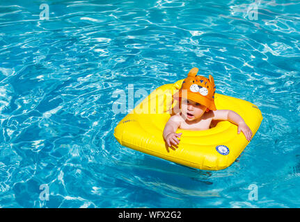 A small baby boy wearing an orange hat happily plays and splashes waving his arms in a swimming pool supported by an inflatable flotation aid - Stock Photo