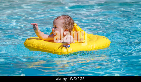 A small baby boy with wet curly hair happily plays and splashes waving his arms in a swimming pool supported by a yellow inflatable flotation aid - Stock Photo
