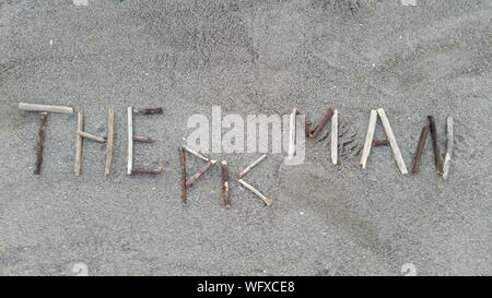 High Angle View Of Text Made From Sticks On Sandy Beach - Stock Photo