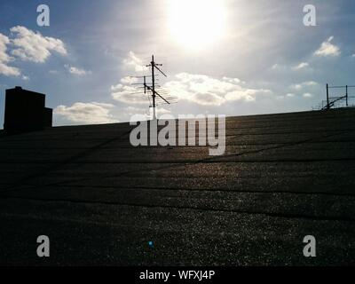 Low Angle View Of Television Aerials On House Roof - Stock Photo