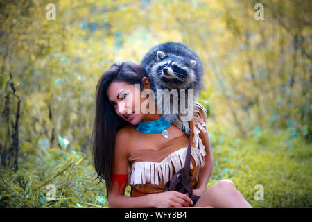 Young Woman In Traditional Clothing Carrying Raccoon In Forest - Stock Photo
