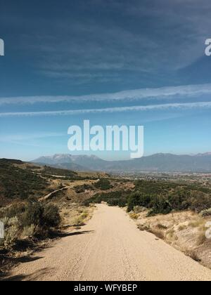 Dirt Road Amidst Landscape Against Sky - Stock Photo