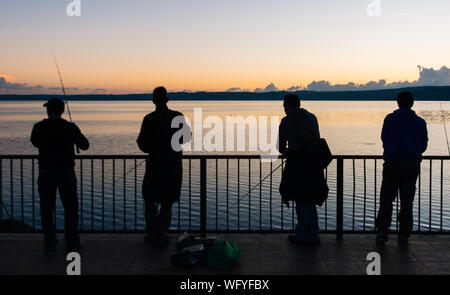 Rear View Of Friends Fishing On Pier Over Lake Bracciano Against Sky During Sunset - Stock Photo
