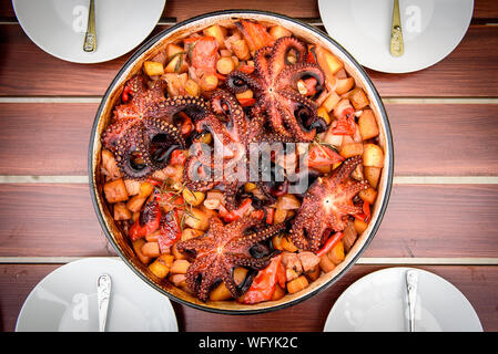 Preparing and Cooking of octopus in traditional Balkan Croatian Greek Mediterranean meal Peka in metal pots called sac sach or sache or a lid. Dish is - Stock Photo