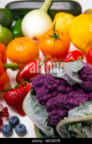 Assorted of fresh fruits and vegetables arranged in a rainbow color pattern over whiate background - Stock Photo