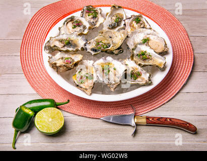 Detail of a plate with fresh shucked oysters with jalapeno & lemon mignonette over wood background - Stock Photo