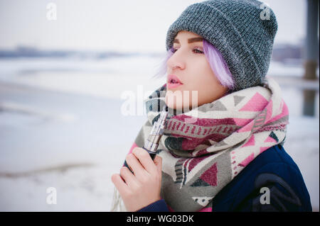 Woman Smoking Electronic Cigarette While Standing On Snow Covered Landscape Against Sky - Stock Photo