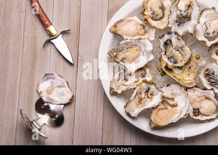 Detail of a plate with fresh shucked oysters from the Canadian west coast over wood background - Stock Photo