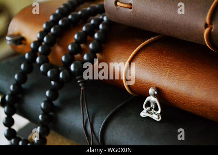 Close-up Of Bead Necklace And Figurine With Books - Stock Photo