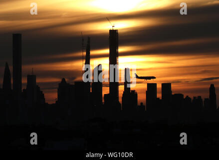 New York, USA. 31st Aug, 2019. An airplane flies by the Manhattan skyline at sunset from Arthur Ashe Stadium at the 2019 US Open Tennis Championships at the USTA Billie Jean King National Tennis Center on Saturday, August 31, 2019 in New York City. Credit: UPI/Alamy Live News - Stock Photo