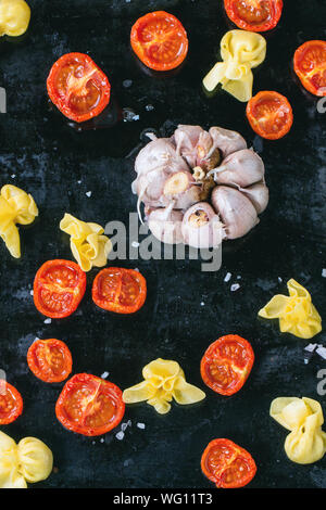 Directly Above Shot Of Sacchettini Pasta With Garlic And Sun Dried Tomatoes On Baking Sheet - Stock Photo