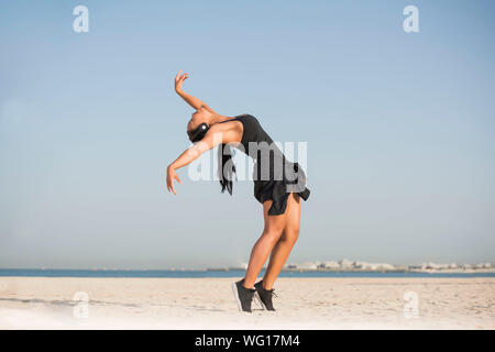 Young Woman Dancing At Beach Against Clear Sky - Stock Photo