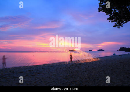 Woman Spinning Wire Wool On Beach Against Sky During Sunset - Stock Photo