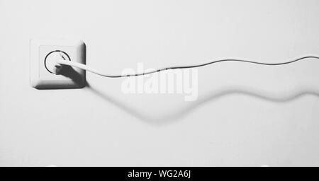 Electrical Plug In Outlet On White Wall - Stock Photo