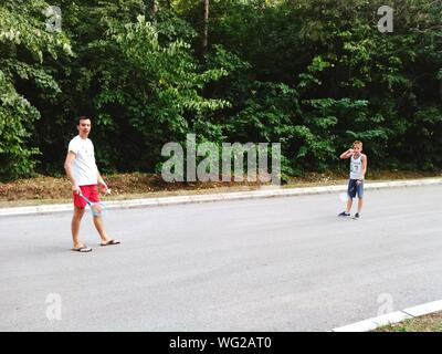 Father And Son Playing Badminton On Road Against Trees - Stock Photo