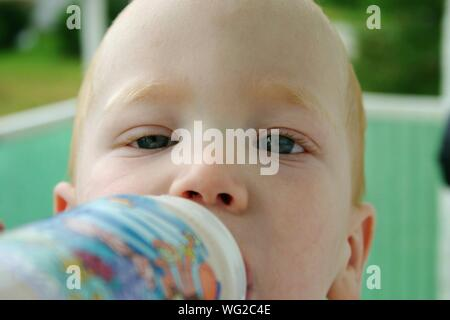 Close-up Portrait Of Cute Boy Drinking Milk - Stock Photo