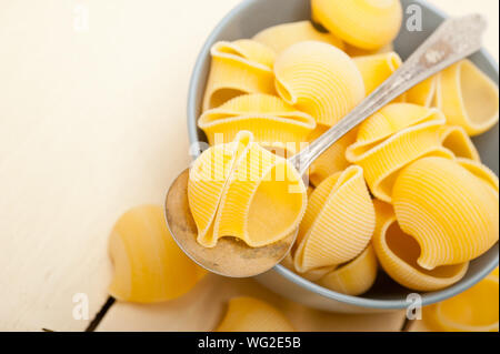 Conchiglie Pasta In Bowl With Spoon On Table - Stock Photo