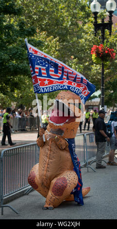 "Boston, MA, USA.  31st August 2019.  Hundreds march in the Straight Pride Parade through Boston, MA.  The marchers, supporters of U.S. President Donald Trump, were outnumbered by anti-Trump and gay rights supporters. The Straight Pride march was organized by the newly formed ""Super Happy Fun America"", who organized the Boston event as a response to gay pride parades that have been held in most major U.S, cities. Photo shows a man dressed as a dinosaur carrying a Trump 2020 on Boylston Street at the start of the parade. Credit Chuck Nacke / Alamy Live News - Stock Photo"