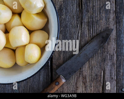 Directly Above Shot Of Peeled Boiled Potatoes In Bowl By Knife On Table - Stock Photo
