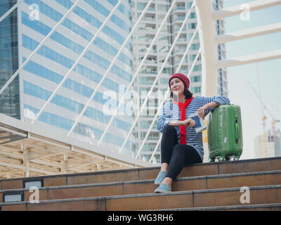 Happy Teenage Girl With Suitcase Sitting On Steps Against Building - Stock Photo