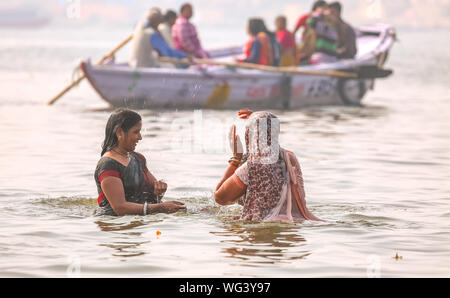 Indian women take holy dip in the Ganges river at Varanasi with view of a boat with tourist and pilgrims - Stock Photo