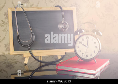 Close-up Of Alarm Clock With Blackboard And Stethoscope On Table - Stock Photo