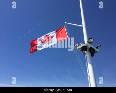 Low Angle View Of Canadian Flag Against Blue Sky - Stock Photo