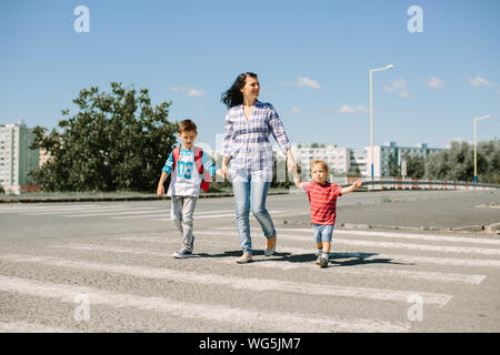 Mother And Children Walking On Zebra Crossing - Stock Photo