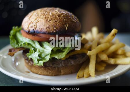 Close-up Of Burger With French Fries Served In Plate - Stock Photo