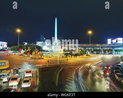Traffic On Illuminated City Street By Obelisk Against Sky At Night - Stock Photo