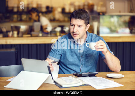 Successful new restaurant owner checking monthly reports online on tablet – middle aged man calculating bills and expenses of his small business - Stock Photo