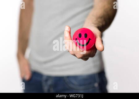 Midsection Of Man Holding Red Ball With Smiley Face Against White Background - Stock Photo