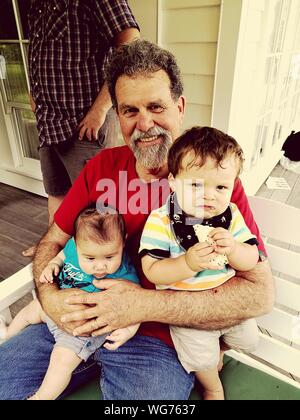 Portrait Of Mature Man With Grandsons Sitting On Bench At Porch - Stock Photo