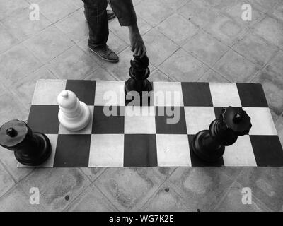 Cropped Image Of Person Holding Chess Piece Over Chess Board On Street - Stock Photo