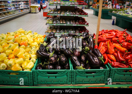 Red sweet peppers, eggplants and yellow sweet peppers on the fruits and vegetables aisle in a store - Stock Photo