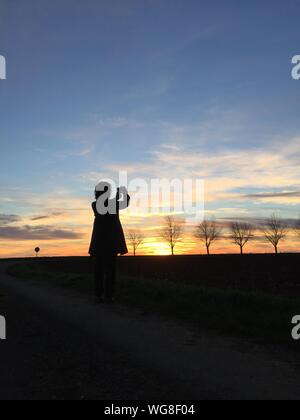 Silhouette Woman Photographing Sunset On Field - Stock Photo