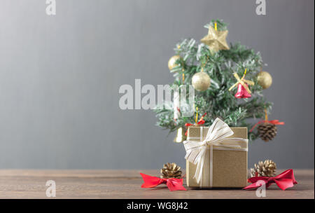 Gold gift box and Fir tree with sign accessory season.Decoration & Ornament of Happy new year and Merry Christmas winter concept.Blur grey background - Stock Photo